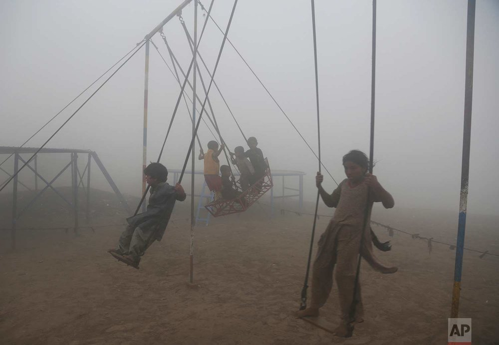 Children ride swings in a playground engulfed by smog in Lahore, Pakistan, Saturday, Nov. 11, 2017. Officials said smog has enveloped much of the country, causing highway accidents and respiratory problems, and forcing many residents to stay home. (AP Photo/K.M. Chaudary)