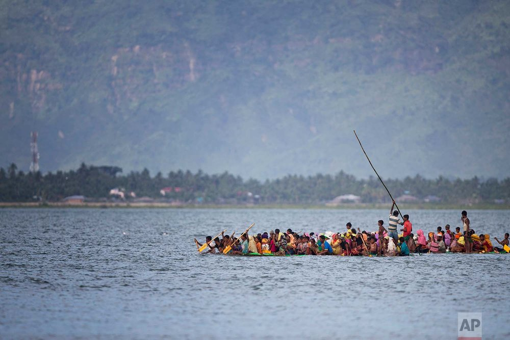 Rohingya Muslims aboard a makeshift raft made with plastic containers cross the Naf River from Myanmar into Bangladesh, near Shah Porir Dwip, Bangladesh, Sunday, Nov. 12, 2017. (AP Photo/A.M. Ahad)