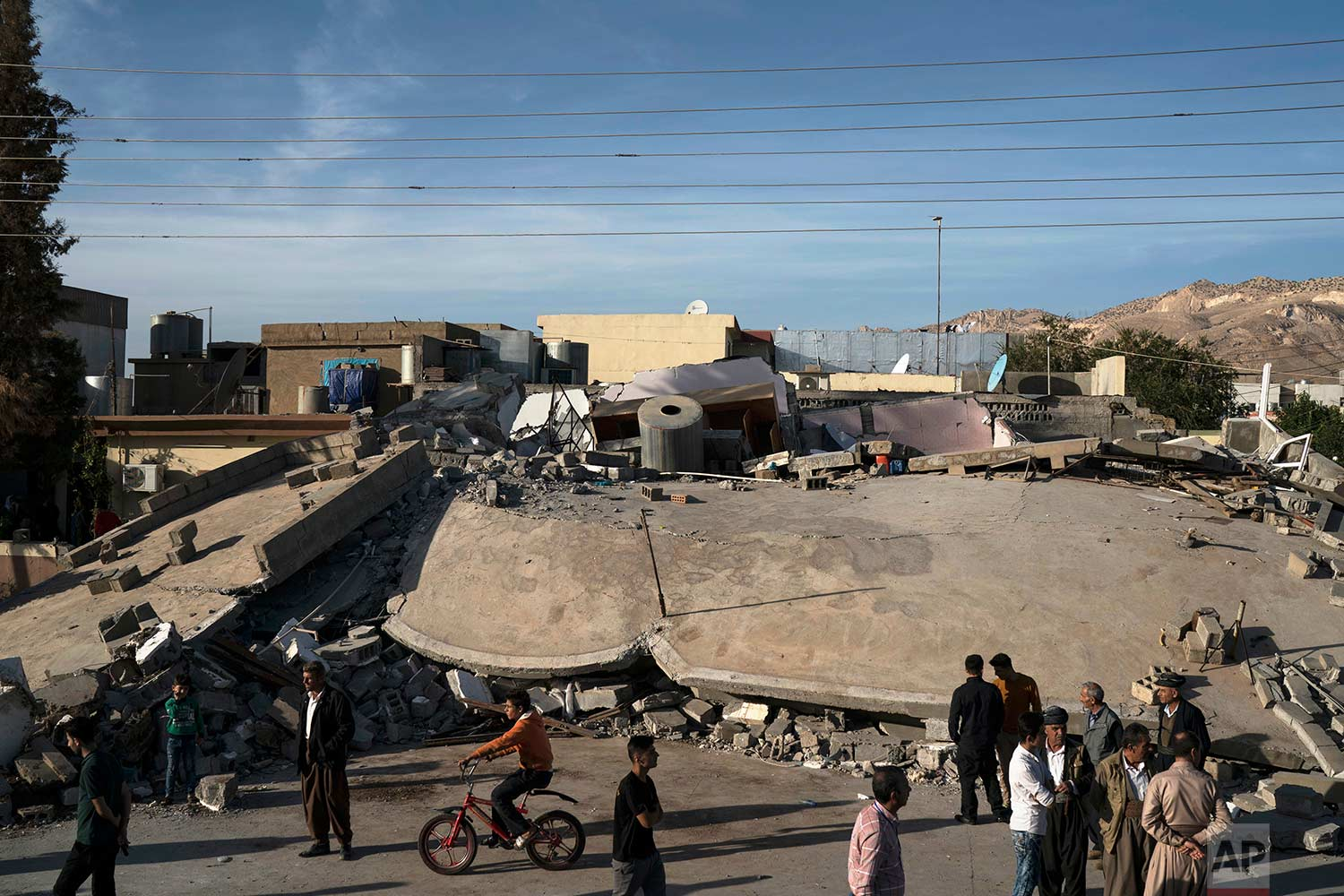 People walk next to a destroyed building after an earthquake in the city of Darbandikhan, northern Iraq, Monday, Nov. 13, 2017. (AP Photo/Felipe Dana)