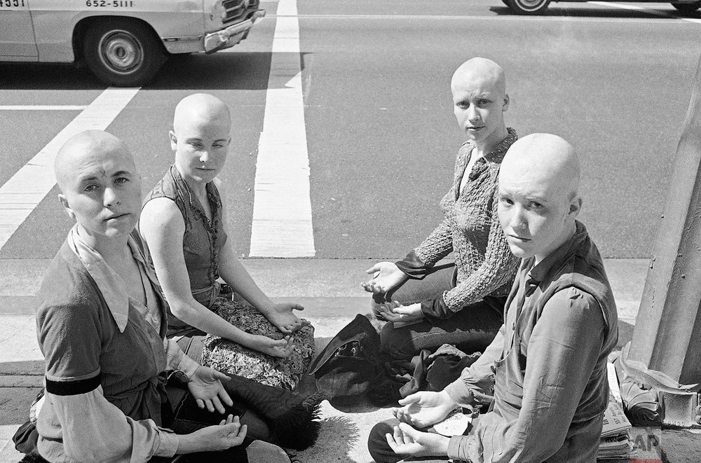 """Four young women members of the Charles Manson """"family"""" kneel on the sidewalk outside the Los Angeles at Hall of Justice, March 29, 1971 with their heads shaved. They've kept a vigil at the building throughout the long trial in which Manson and three other women were convicted of slaying actress Sharon Tate and six others. Left to right: Cathy Gillies, Kitty Lutesinger, Sandy Good, Brenda McCann. Jurors were believed near a verdict on the penalty to be imposed on the defendants. (AP Photo/Wally Fong)"""