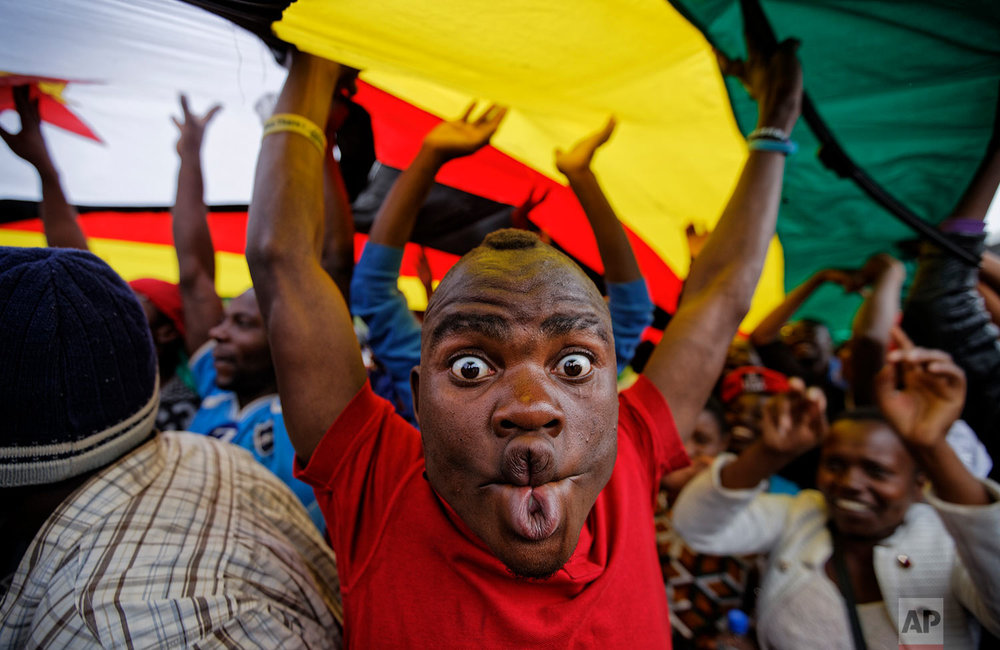 A happy protester pulls a face as he and others stand under a large national flag, at a demonstration of tens of thousands at Zimbabwe Grounds in Harare, Zimbabwe Saturday, Nov. 18, 2017. Opponents of Mugabe are demonstrating for the ouster of the 93-year-old leader who is virtually powerless and deserted by most of his allies. (AP Photo/Ben Curtis)