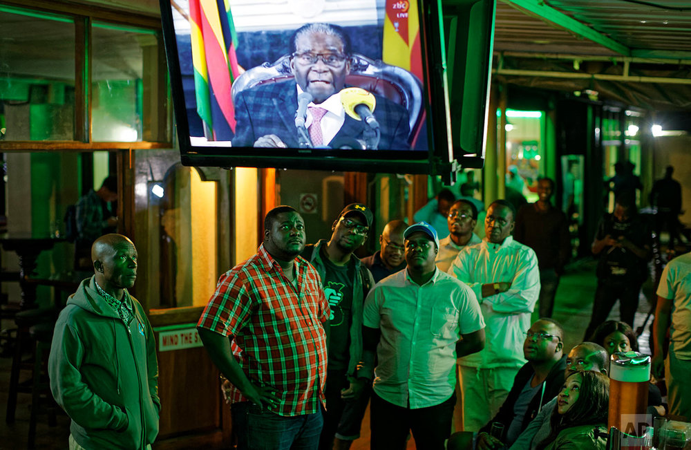 Zimbabweans watch a televised address to the nation by President Robert Mugabe at a bar in downtown Harare, Zimbabwe Sunday, Nov. 19, 2017. Zimbabwe's President Robert Mugabe has baffled the country by ending his address on national television without announcing his resignation. (AP Photo/Ben Curtis)