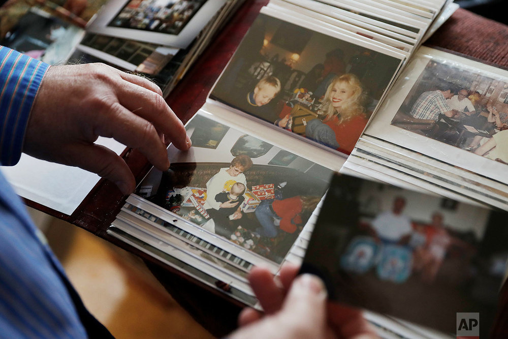Kyle Graves flips though family photos in his home. (AP Photo/David Goldman)