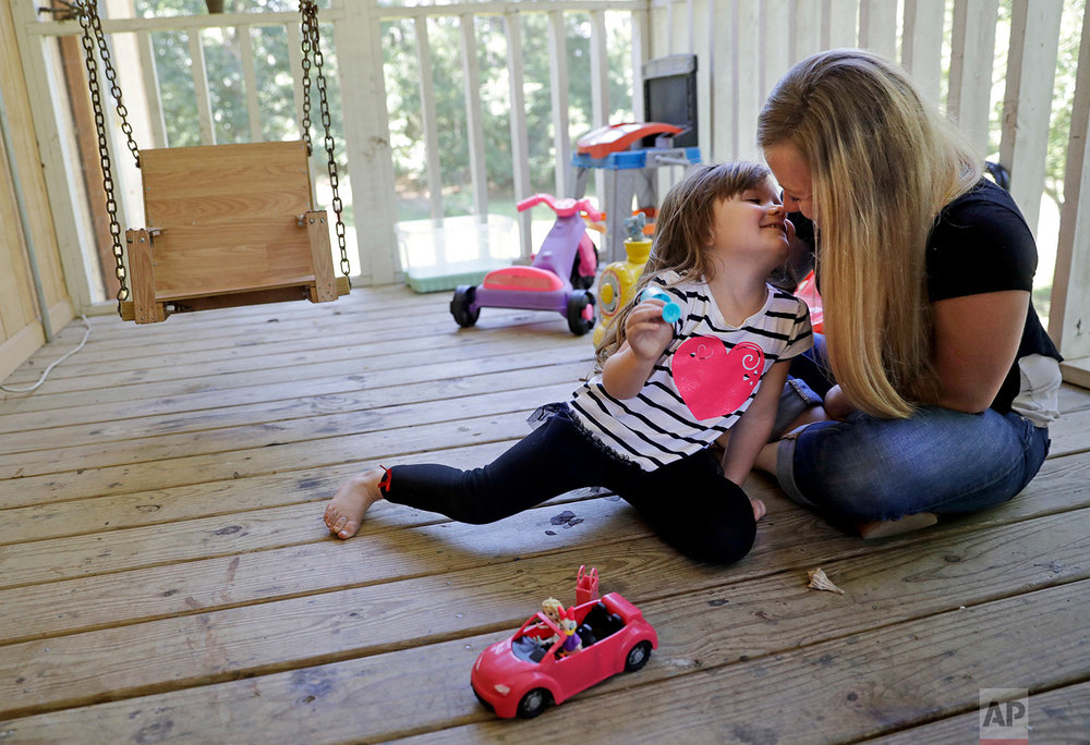 "Whitney Duncan, right, plays with her daughter, Deklyn, 3, while visiting her at the home she's staying at with her grandmother in Jasper, Ga., Monday, June 26, 2017. Duncan was given a choice after failing a drug screening in 2016; lose her daughter to foster care or temporarily give her to a family member while she enters the county's two-year family drug court program to help with her opioid addiction. ""It took a while for me to be ok with me being an addict,"" said Duncan of her recovery. ""I can actually dream again and smile at my future instead of not caring about my future. There is one to be had and it's not going to be a jail cell and it's not going to be death."" (AP Photo/David Goldman)"