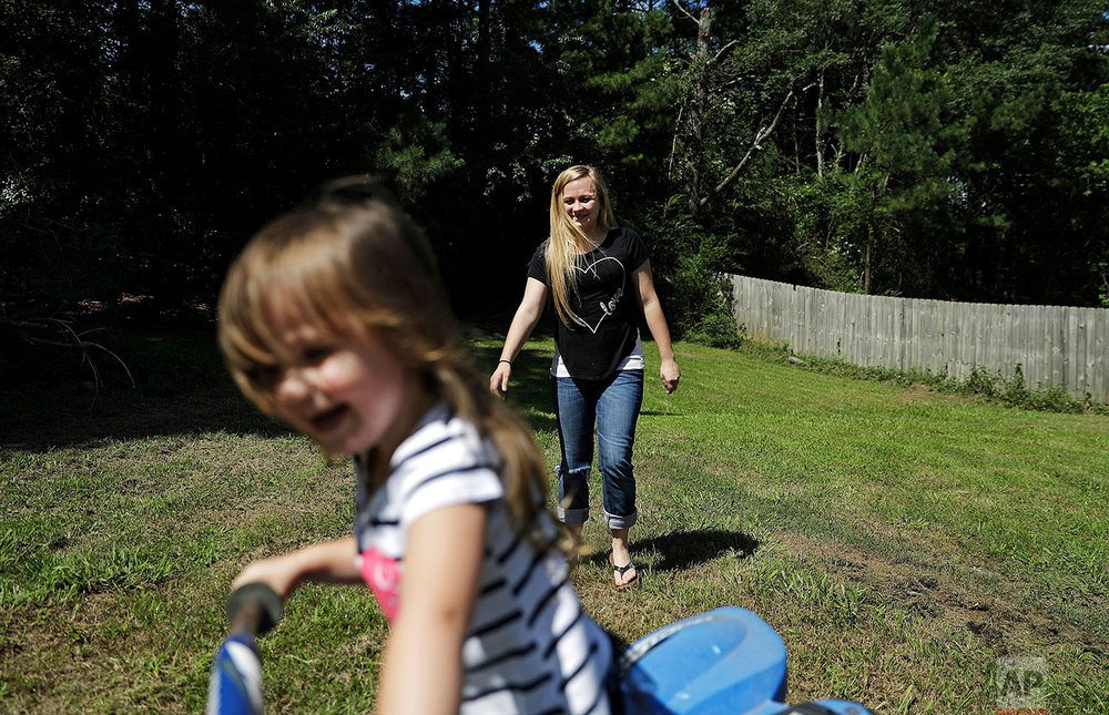 Whitney Duncan, right, plays with her daughter Deklyn, 3, while visiting her at the home she's staying at with her grandmother in Jasper, Ga., Monday, June 26, 2017. Duncan was given a choice after failing a drug screening in 2016; lose their daughter to foster care or temporarily give her to a family member while she and her husband enter the county's two-year family drug court program to help with their opioid addiction. Across the United States, the opioid epidemic _ and other types of debilitating substance abuse by parents _ is fueling a surge of children being taken into foster care. One of the most dramatic increases has been in Georgia, where the foster-care population soared from about 7,600 in September 2013 to more than 13,300 this spring. (AP Photo/David Goldman)