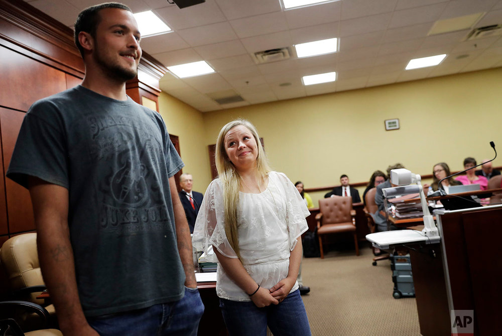 Whitney Duncan, right, smiles at her husband, Dalton, after they were praised by the judge for their progress in the county's family drug court program in Jasper, Ga., Monday, June 26, 2017. They were given a choice after failing a drug screening in 2016; lose their daughter to foster care or temporarily give her to a family member while they enter the two-year program to help with their opioid addiction. (AP Photo/David Goldman)