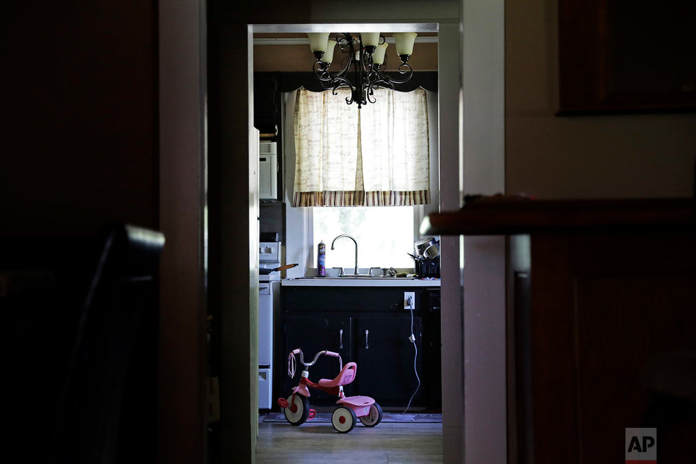 "A tricycle belonging to their daughter sits in the kitchen of Whitney and Dalton Duncan's home in Jasper, Ga., Monday, June 26, 2017. They were given a choice after failing a drug screening in 2016; lose their daughter to foster care or temporarily give her to a family member while they enter the county's two-year family drug court program to help with their opioid addiction. ""At home when she's not there you feel empty. The house feels empty,"" said Whitney Duncan. ""It's just so quiet. You don't want to be there. It's depressing."" (AP Photo/David Goldman)"