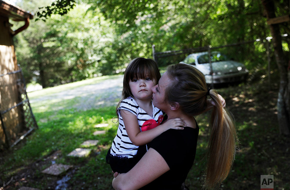 "Whitney Duncan holds her daughter, Deklyn, 3, while visiting her at the home she's staying at with her grandmother in Jasper, Ga., Monday, June 26, 2017. Duncan and her husband were given a choice after failing a drug screening in 2016; lose their daughter to foster care or temporarily give her to a family member while they enter the county's two-year family drug court program to help with their opioid addiction. ""Knowing that I couldn't go pick her up when I wanted to, that I wasn't go to be able to be with her at night time and that my whole world had changed and just realizing what I had done, that was my rock bottom,"" said Duncan. (AP Photo/David Goldman)"