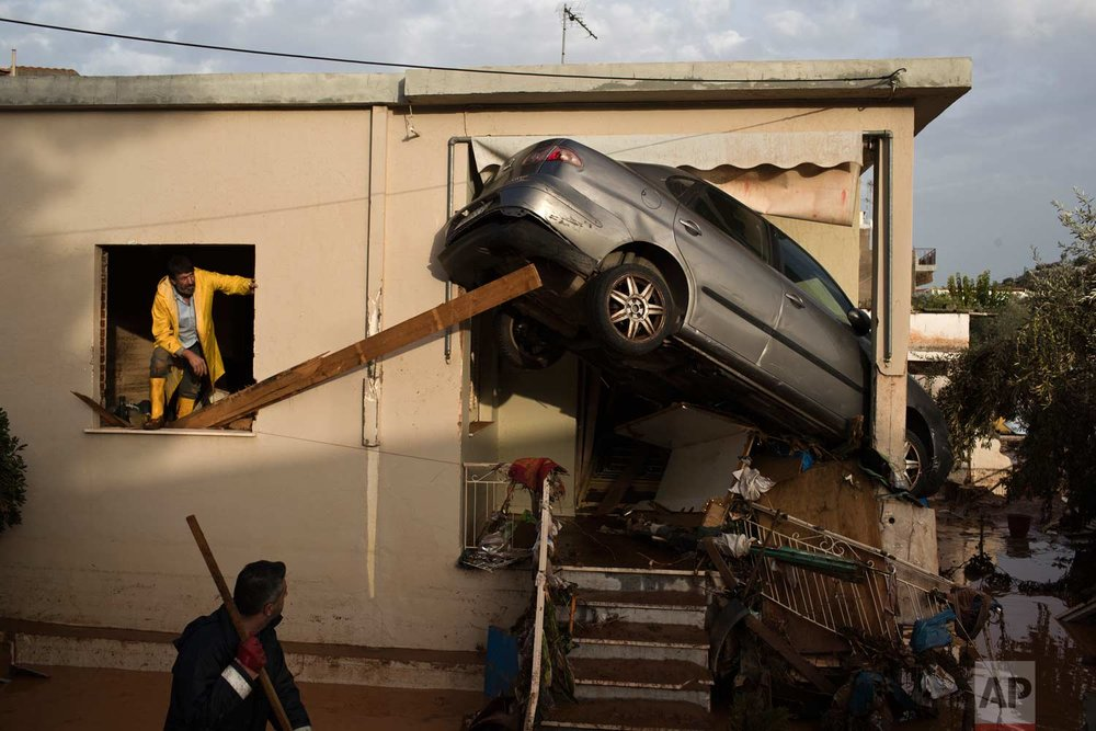 In this Thursday, Nov. 16, 2017 photo, workers try to remove a vehicle wedged into the entrance of a home in the town of Mandra western Athens. A major flash flooding on Wednesday that left at least 21 people dead, turned streets into torrents of mud and debris that swept away cars, collapsed walls and submerged parts of a major highway. (AP Photo/Petros Giannakouris)