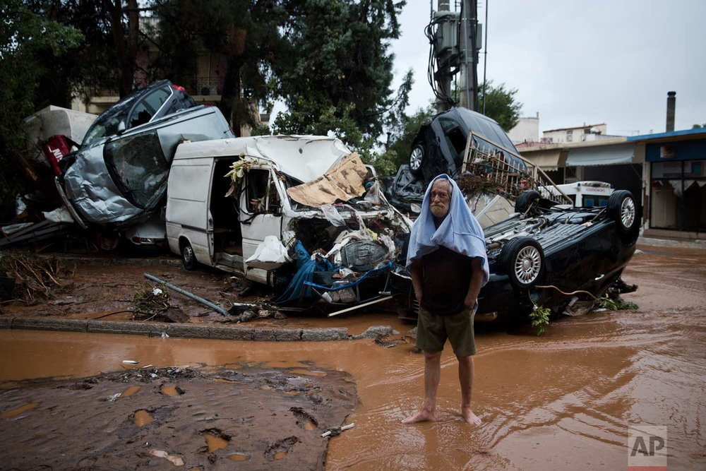 In this Wednesday, Nov. 15, 2017 photo a barefoot Costas Maroulis 62 stands in front of piled up vehicles in the town of Mandra western Athens, following deadly flash floods that hit the area hours before. (AP Photo/Petros Giannakouris)