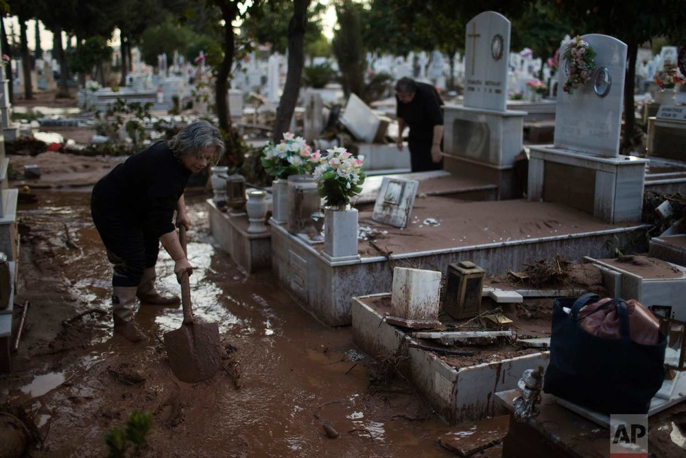 In this Friday, Nov. 17, 2017 photo, Kiriaki Ksanthou cleans mud next to the tombs of her husband and her son in the flood-damaged cemetery of the town of Mandra western Athens, following deadly flash floods that hit the area.(AP Photo/Petros Giannakouris)