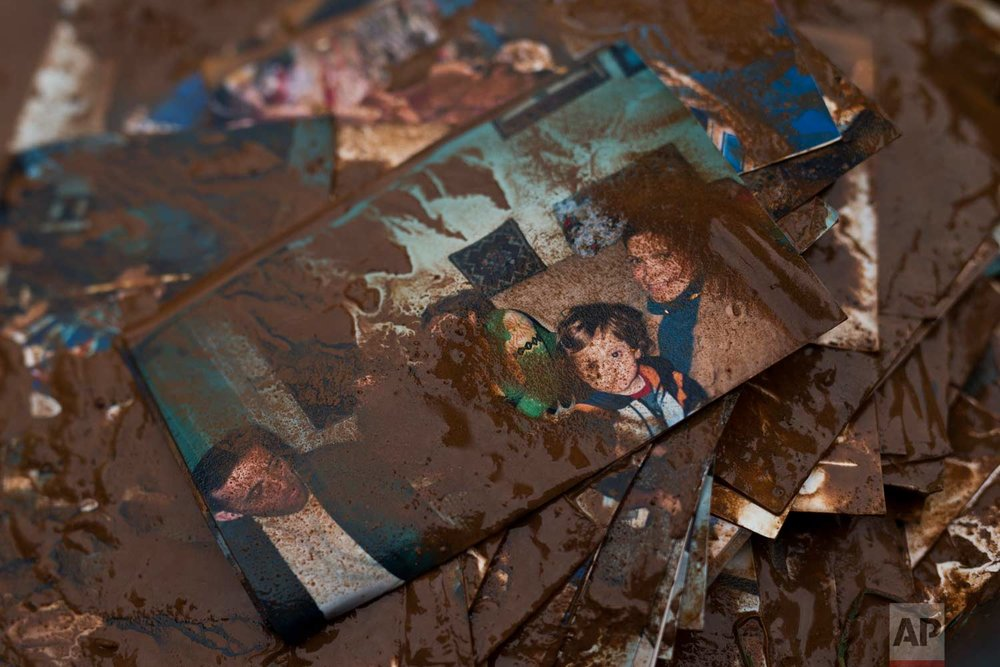 In this Thursday, Nov. 16, 2017 photo, family pictures are covered with mud outside a house in the town of Mandra western Athens, on Thursday, Nov. 16, 2017, following major flash flooding that left at least 21 people dead.(AP Photo/Petros Giannakouris)