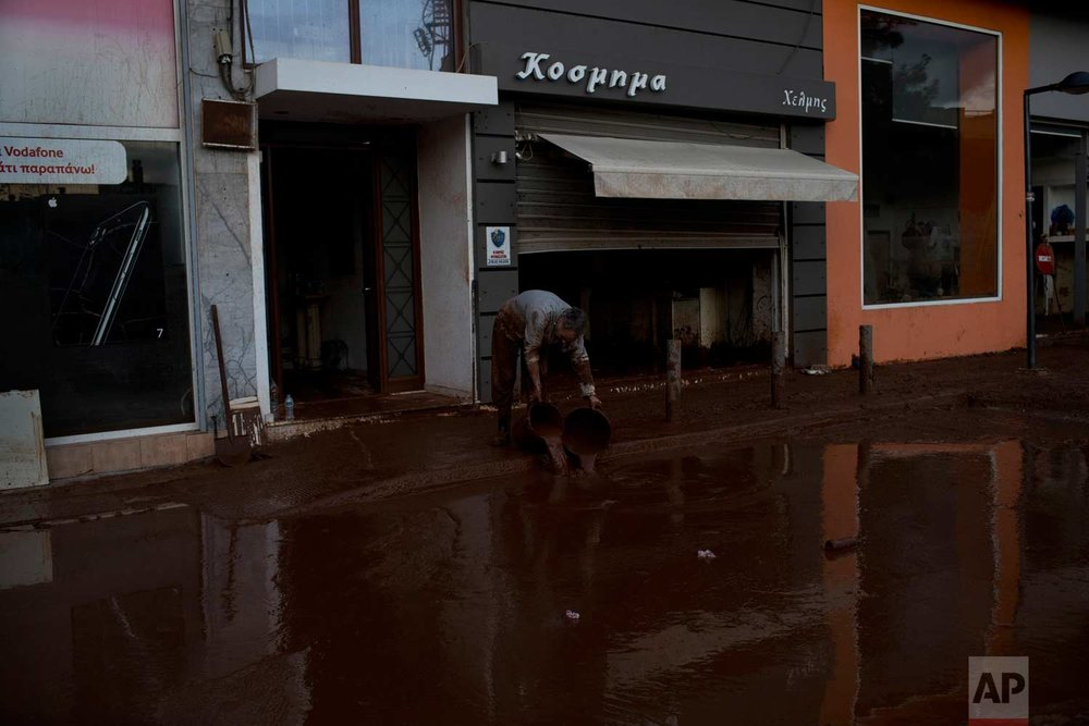 In this Friday , Nov. 17, 2017 photo, a man drops buckets with mud outside his home in the town of Mandra western Athens, on Friday , Nov. 17, 2017 following deadly flash floods that struck near Athens, killing at least 21 people.(AP Photo/Petros Giannakouris)