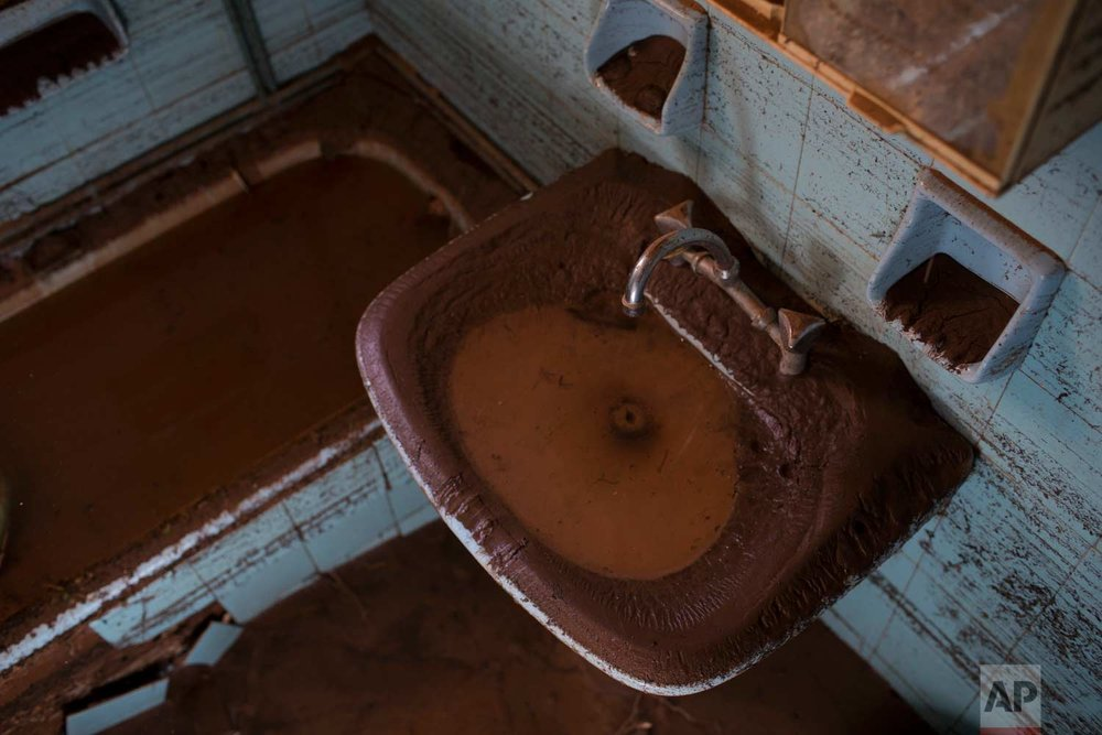 In this Tuesday , Nov. 21, 2017 photo a sink and a bathtub is covered with mud into a flood-damaged home in the town of Mandra , west of Athens. (AP Photo/Petros Giannakouris)