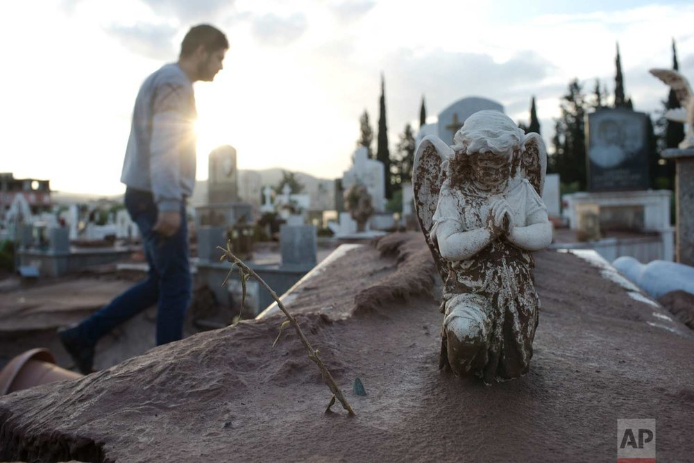 In this Friday , Nov. 17, 2017 photo, a man walks past a tomb covered with mud as he is searching the tomb of his grandmother in the flood-damaged cemetery of the town of Mandra western Athens, on Friday , Nov. 17, 2017, following deadly flash floods that struck near Athens, killing 21. (AP Photo/Petros Giannakouris)