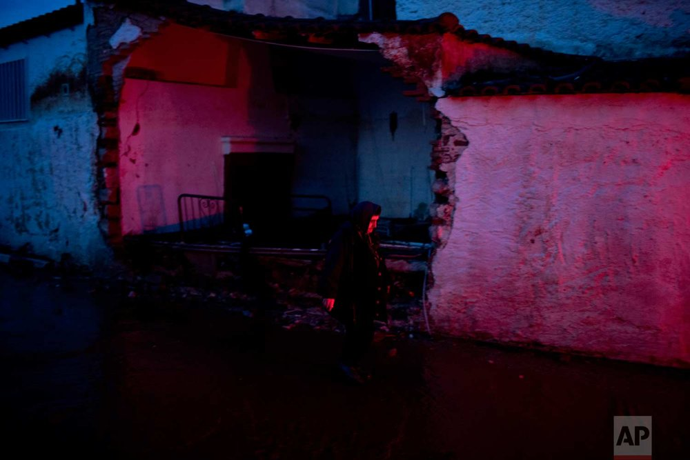 In this Friday, Nov. 17, 2017 photo, an elderly woman walks in front of a flood-damaged house in the town of Mandra western Athens, on Friday , Nov. 17, 2017. (AP Photo/Petros Giannakouris)