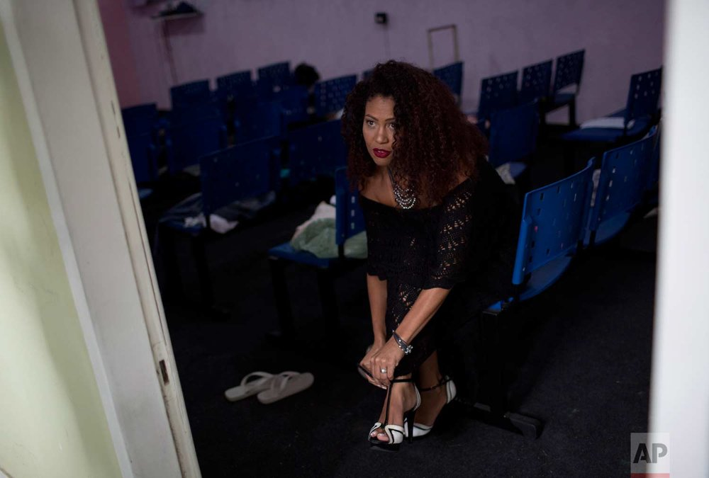 "Inmate Michelle Rangel, current ""Miss Talavera Bruce"" beauty pageant title holder puts on her heels before defending her title at Talavarera Bruce penitentiary in Rio de Janeiro, Brazil, early Thursday, Nov. 23, 2017. (AP Photo/Silvia Izquierdo)"