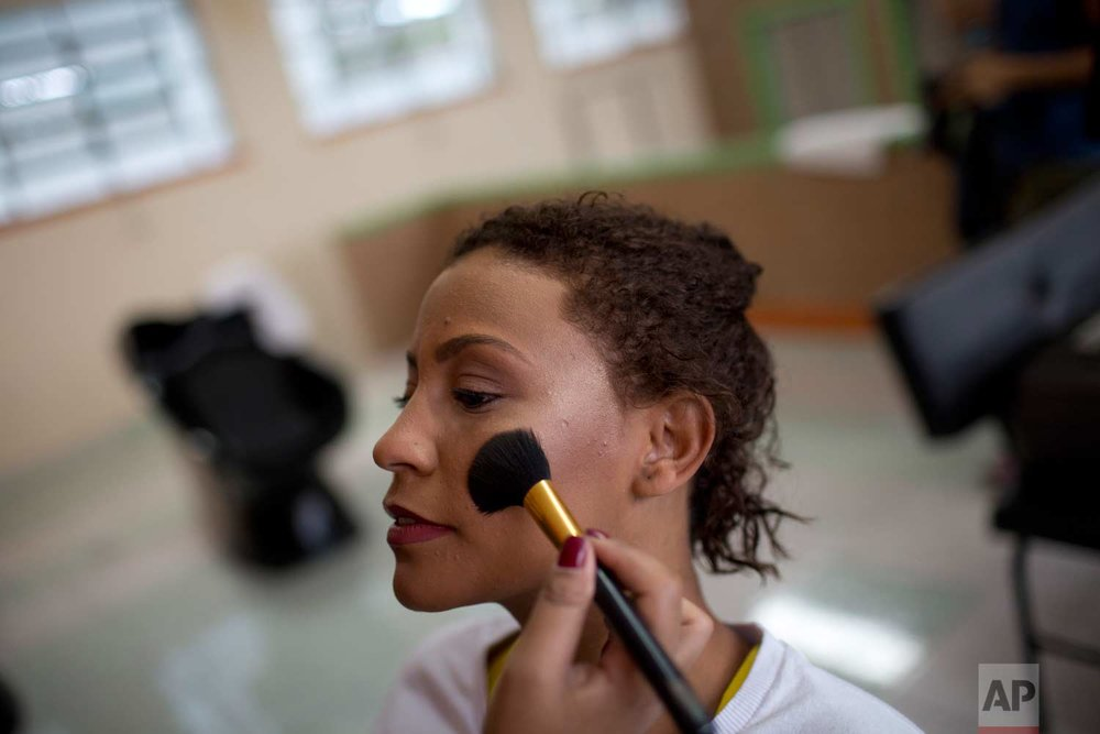 An inmate holds still as an event volunteer applies her blush for an annual beauty contest at Talavera Bruce penitentiary in Rio de Janeiro, Brazil, early Thursday, Nov. 23, 2017. (AP Photo/Silvia Izquierdo)