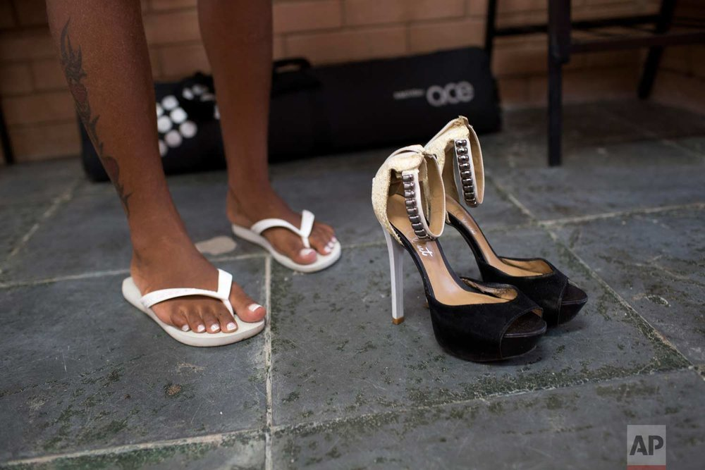 A female inmate wearing her jail-issued flip flops prepares to change to heels for the annual beauty contest at Talavera Bruce penitentiary in Rio de Janeiro, Brazil, early Thursday, Nov. 23, 2017. (AP Photo/Silvia Izquierdo)