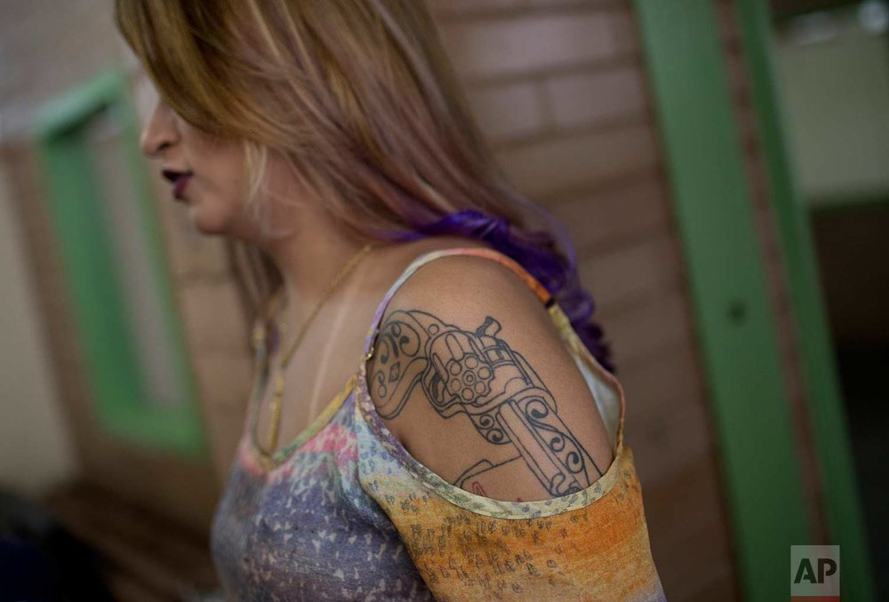 A tattoo of a weapon covers the arm of a female inmate waiting to compete in the annual beauty contest at Talavera Bruce penitentiary in Rio de Janeiro, Brazil, early Thursday, Nov. 23, 2017. (AP Photo/Silvia Izquierdo)