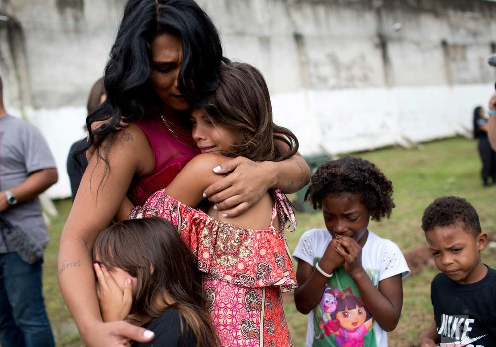 Female inmate Rossana Goncalves with four of her five children cry as they reunite on the sidelines of competing in her jail's annual beauty contest at Talavera Bruce penitentiary in Rio de Janeiro, Brazil, early Thursday, Nov. 23, 2017. (AP Photo/Silvia Izquierdo)