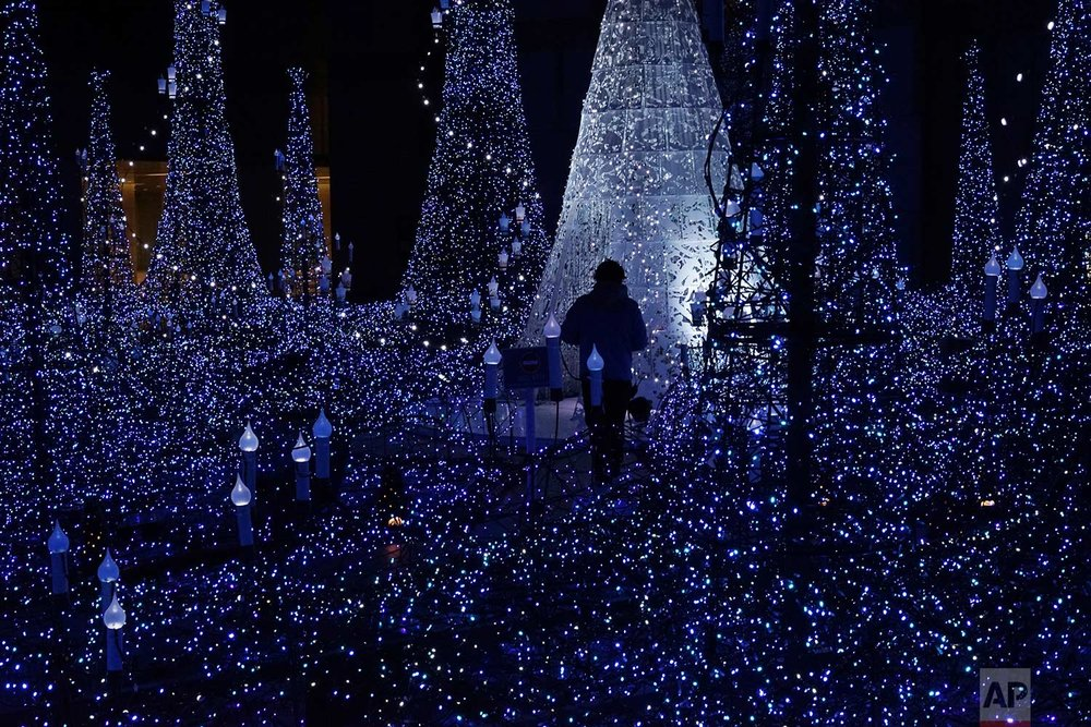 Staff walk through the annual year end illumination in Shiodome district , in Tokyo, Thursday, Nov. 23, 2017. (AP Photo/Eugene Hoshiko)