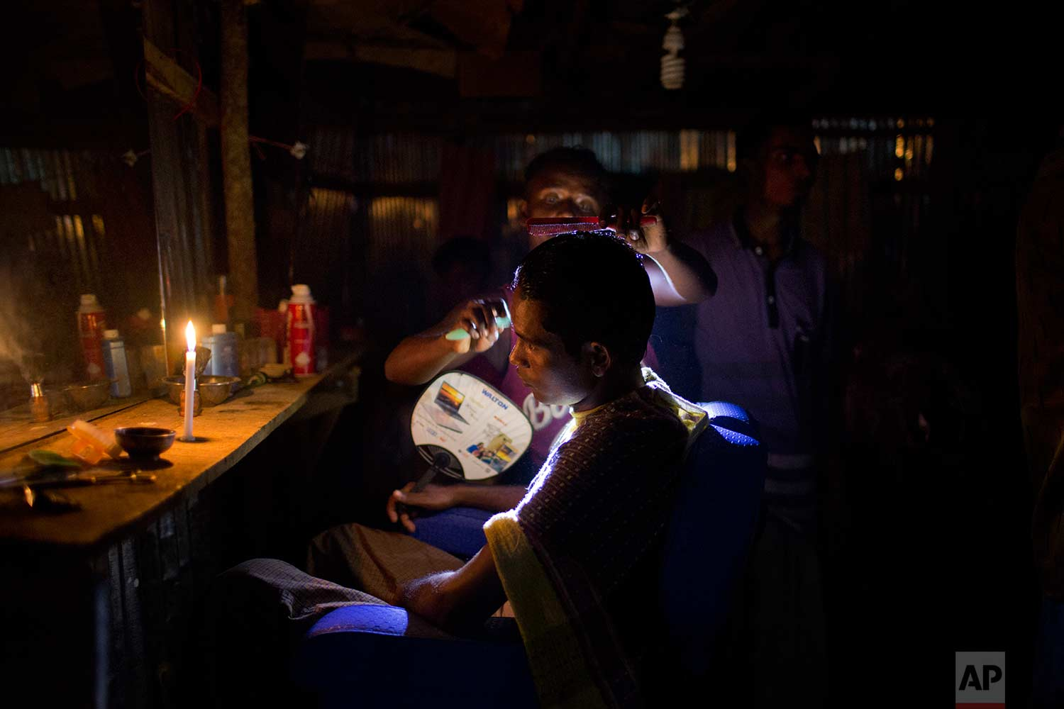 A Rohingya Muslim gets his hair cut in a makeshift barber shop that is lit with a candle and a torch light at Jamtoli refugee camp, Friday, Nov. 24, 2017, in Bangladesh. (AP Photo/Wong Maye-E)