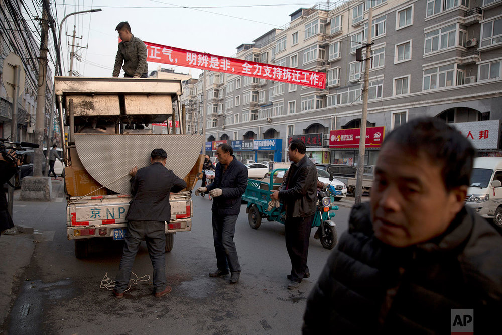 "Workers load kitchen equipment near propaganda slogans at left that read: ""Carry forward righteousness, Differentiate right and wrong, Fully support eviction work"" onto a truck from a restaurant that's closed by the eviction in the outskirts of Beijing Monday, Nov. 27, 2017.  (AP Photo/Ng Han Guan)"