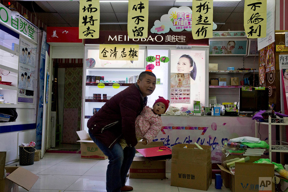 The owner of a cosmetic shop holds his grandchild near sale notices as he tries to sell his wares before leaving the outskirts of Beijing, China, Monday, Nov. 27, 2017. (AP Photo/Ng Han Guan)