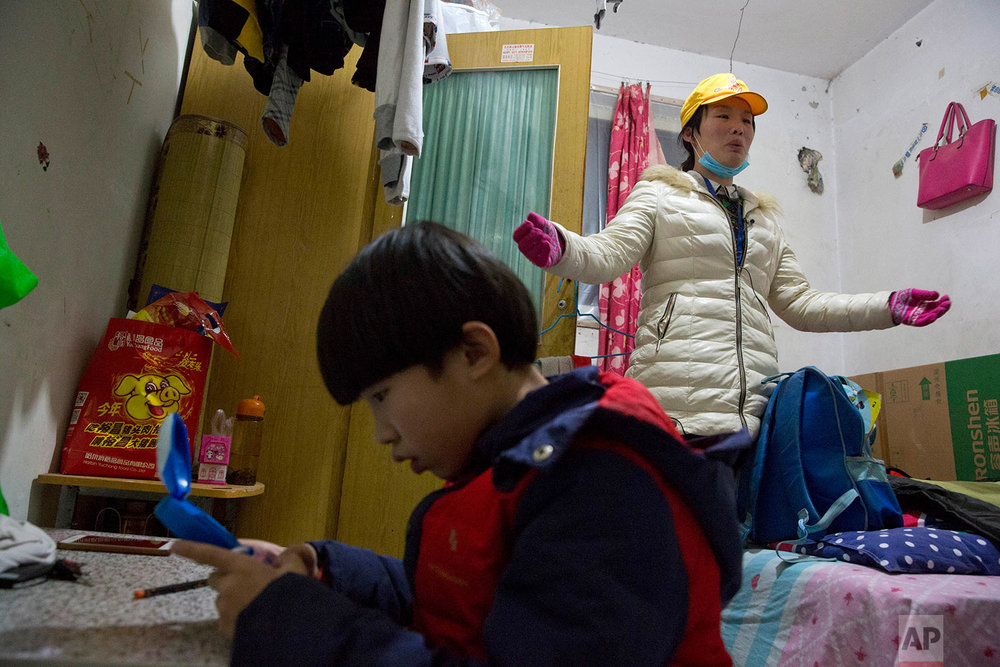 Zhou Xinci, right, a migrant from Heilongjiang, talks about her fears of being evicted, as her son sits at left, in the outskirts of Beijing, China, Monday, Nov. 27, 2017. (AP Photo/Ng Han Guan)