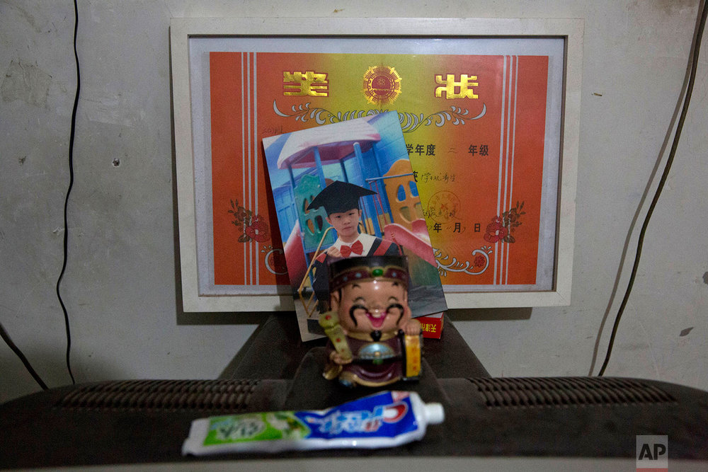 A graduation photo and certificate is displayed in the home of Zhou Xinci in her rented apartment in the outskirts of Beijing, China, Monday, Nov. 27, 2017.  (AP Photo/Ng Han Guan)