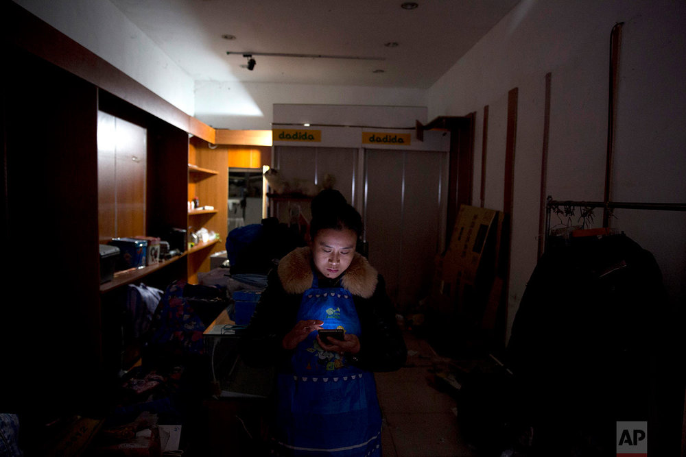 A migrant shop owner looks through her mobile phone for online video of recent evictions as she stands in the middle of of her store in Beijing Monday, Nov. 27, 2017. Authorities in Beijing have been evicting domestic migrant workers from the capital in droves, triggering a public outcry over the harsh treatment of people the city depends on to build their skyscrapers, care for their children and take on other lowly-paid work. (AP Photo/Ng Han Guan)