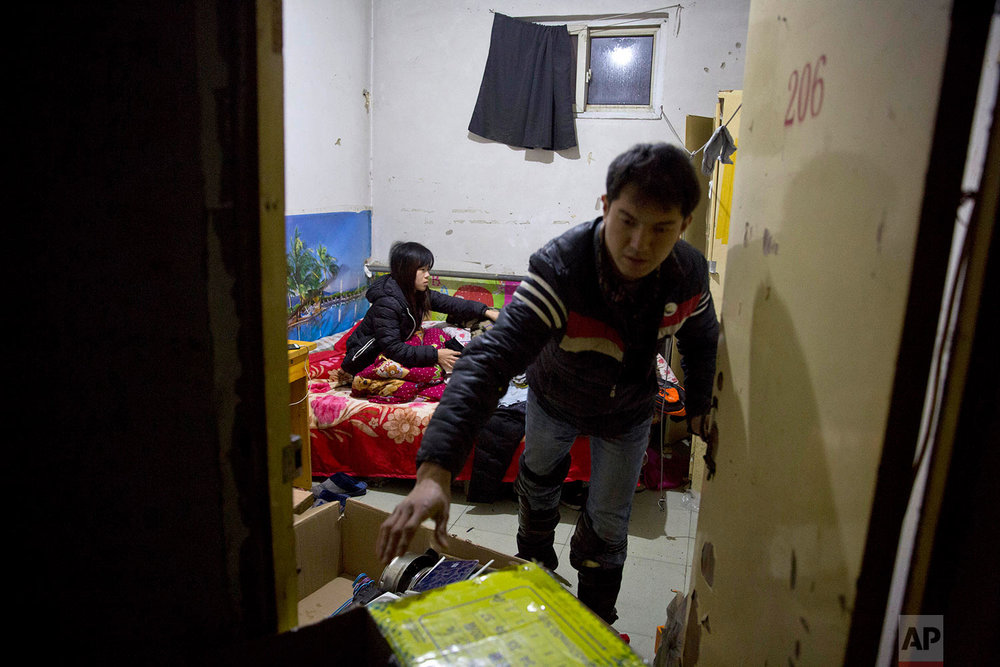 A couple of migrant workers prepare to leave their apartment ahead of an eviction deadline in the outskirts of Beijing, China, Monday, Nov. 27, 2017.  (AP Photo/Ng Han Guan)