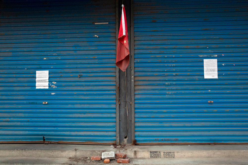 Eviction notices are pasted on shuttered stores near a Chinese national flag on the outskirts of Beijing, China, Monday, Nov. 27, 2017. Authorities in Beijing have been evicting domestic migrant workers from the capital in droves, triggering a public outcry over the harsh treatment of people the city depends on to build their skyscrapers, care for their children and take on other lowly-paid work. (AP Photo/Ng Han Guan)