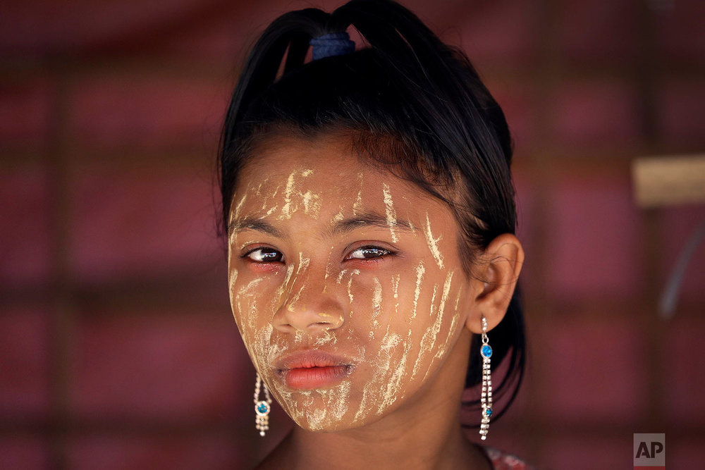 """A Rohingya girl with her face covered in """"thanaka"""", a comestic paste from ground bark, stands in her family's tent on Tuesday, Nov. 21, 2017, in Kutupalong refugee camp in Bangladesh. Since late August, more than 620,000 Rohingya have fled Myanmar's Rakhine state into neighboring Bangladesh, seeking safety from what the military described as """"clearance operations."""" The United Nations and others have said the military's actions appeared to be a campaign of """"ethnic cleansing,"""" using acts of violence and intimidation and burning down homes to force the Rohingya to leave their communities. (AP Photo/Wong Maye-E)"""