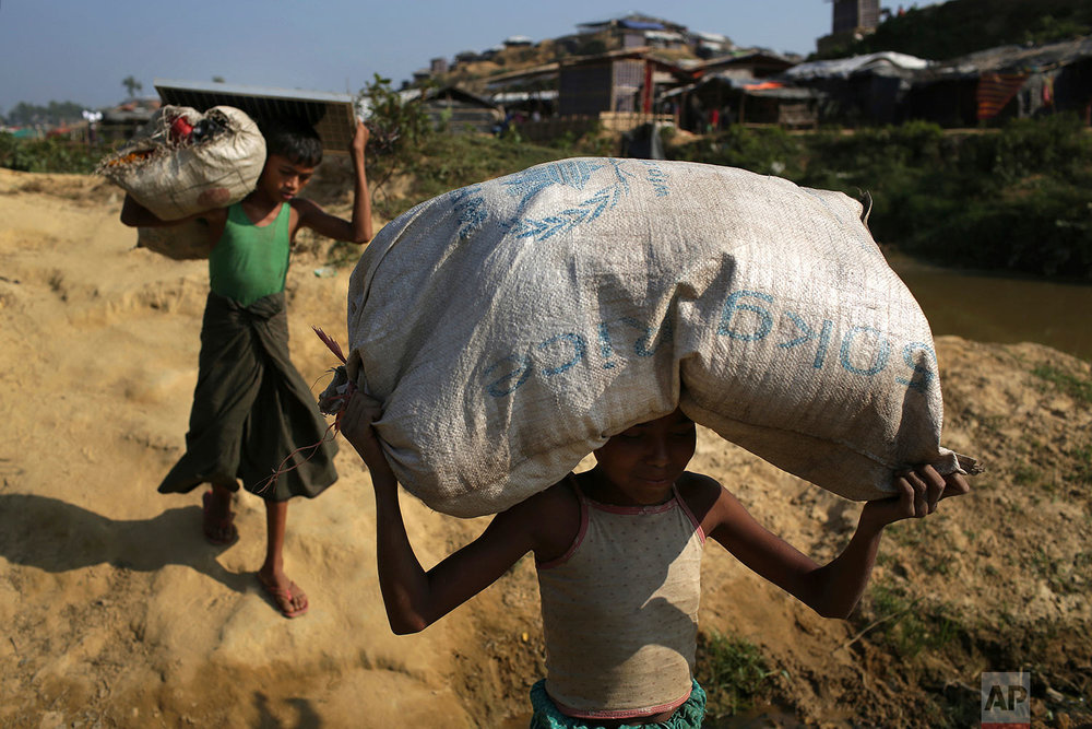 """Rohingya Muslim children carry rice and a solar panel which they collected from an aid distribution center on Tuesday, Nov. 21, 2017, in Kutupalong refugee camp in Bangladesh. Since late August, more than 620,000 Rohingya have fled Myanmar's Rakhine state into neighboring Bangladesh, seeking safety from what the military described as """"clearance operations."""" The United Nations and others have said the military's actions appeared to be a campaign of """"ethnic cleansing,"""" using acts of violence and intimidation and burning down homes to force the Rohingya to leave their communities. (AP Photo/Wong Maye-E)"""