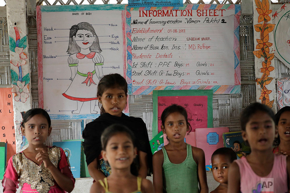 "Rohingya Muslim children recite poems in a makeshift school at the Thaingkhali refugee camp on Wednesday, Nov. 22, 2017, in Bangladesh. Since late August, more than 620,000 Rohingya have fled Myanmar's Rakhine state into neighboring Bangladesh, seeking safety from what the military described as ""clearance operations."" The United Nations and others have said the military's actions appeared to be a campaign of ""ethnic cleansing,"" using acts of violence and intimidation and burning down homes to force the Rohingya to leave their communities. (AP Photo/Wong Maye-E)"