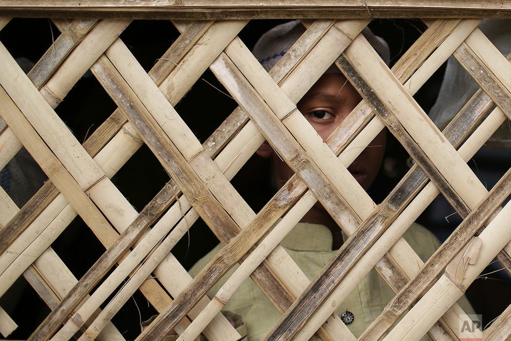 """In this Nov. 24, 2017, file photo, a young Rohingya Muslim boy looks out from a makeshift mosque before Friday prayers in Jamtoli refugee camp, in Bangladesh. Since late August, more than 620,000 Rohingya have fled Myanmar's Rakhine state into neighboring Bangladesh, seeking safety from what the military described as """"clearance operations."""" The United Nations and others have said the military's actions appeared to be a campaign of """"ethnic cleansing,"""" using acts of violence and intimidation and burning down homes to force the Rohingya to leave their communities. (AP Photo/Wong Maye-E, File)"""