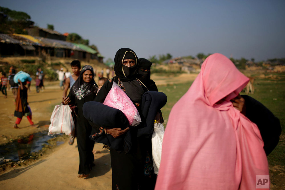 """Rohingya Muslim women carry blankets and other supplies they collected from aid distribution centers in Kutupalong refugee camp in Bangladesh, Tuesday, Nov. 21, 2017. Since late August, more than 620,000 Rohingya have fled Myanmar's Rakhine state into neighboring Bangladesh, seeking safety from what the military described as """"clearance operations."""" The United Nations and others have said the military's actions appeared to be a campaign of """"ethnic cleansing,"""" using acts of violence and intimidation and burning down homes to force the Rohingya to leave their communities. (AP Photo/Wong Maye-E)"""