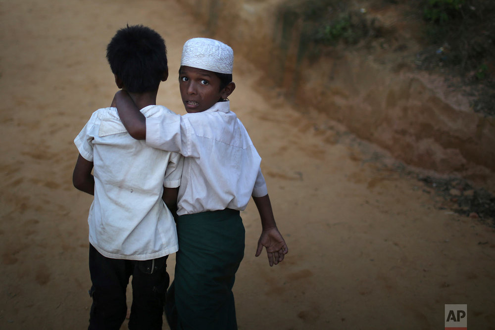 """A Rohingya Muslim boy looks back as he walks with his friend in Kutupalong refugee camp on Saturday, Nov. 25, 2017, in Bangladesh.  The United Nations and others have said the military's actions appeared to be a campaign of """"ethnic cleansing,"""" using acts of violence and intimidation and burning down homes to force the Rohingya to leave their communities, with more than 600,000 Rohingya fleeing to Bangladesh. (AP Photo/Wong Maye-E)"""