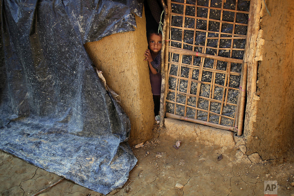 """A Rohingya Muslim child peeks out of his family's home made from mud on Tuesday, Nov. 21, 2017, in Kutupalong refugee camp in Bangladesh. Since late August, more than 620,000 Rohingya have fled Myanmar's Rakhine state into neighboring Bangladesh, seeking safety from what the military described as """"clearance operations."""" The United Nations and others have said the military's actions appeared to be a campaign of """"ethnic cleansing,"""" using acts of violence and intimidation and burning down homes to force the Rohingya to leave their communities. (AP Photo/Wong Maye-E)"""