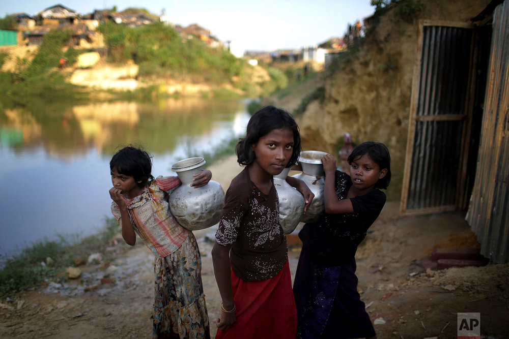 """In this Sunday, Nov. 19, 2017, photo, Rohingya Muslim girls carry water pots in Kutupalong refugee camp in Bangladesh.  More than 620,000 Rohingya have fled Rakhine for neighbouring Bangladesh since late August 2017, when the military launched what it called """"clearance operations"""" in response to insurgent attacks. (AP Photo/Wong Maye-E)"""