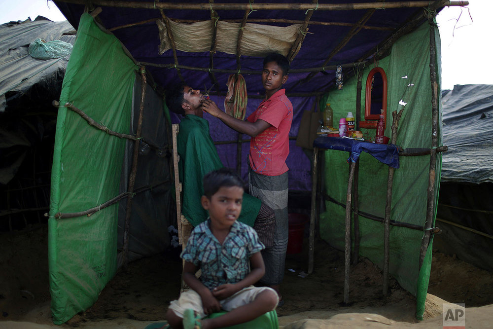 """In this Sunday, Nov. 19, 2017, photo, a Rohingya Muslim child sits in front of a barber's tent in Kutupalong refugee camp in Bangladesh.  More than 620,000 Rohingya have fled Rakhine for neighbouring Bangladesh since late August 2017, when the military launched what it called """"clearance operations"""" in response to insurgent attacks.(AP Photo/Wong Maye-E)"""