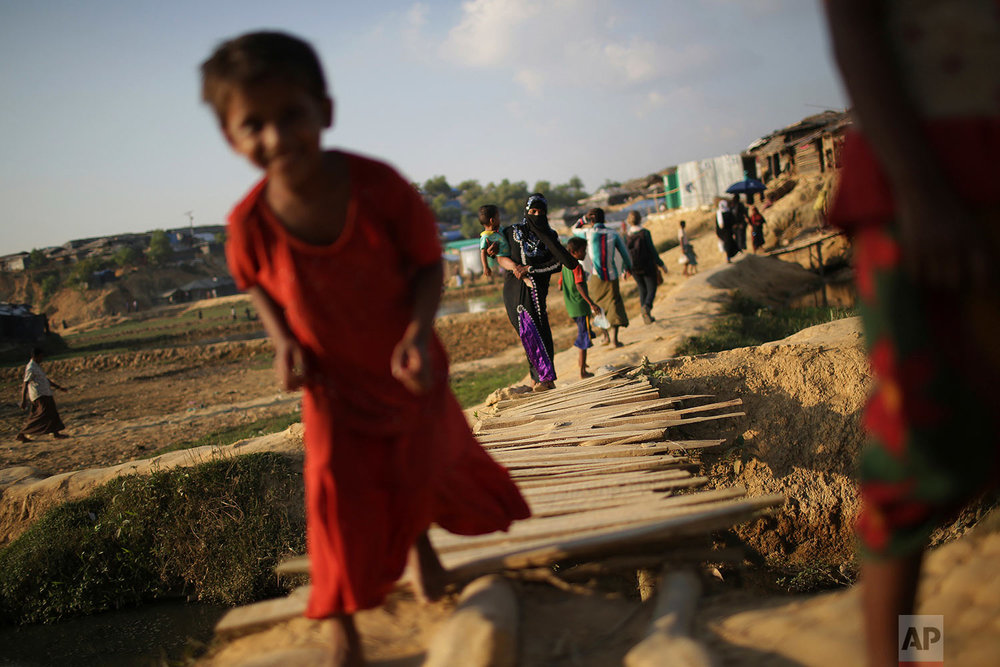 """In this Sunday, Nov. 19, 2017, photo, Rohingya Muslims cross a wooden bridge as they make their way through Kutupalong refugee camp in Bangladesh. More than 620,000 Rohingya have fled Rakhine for neighbouring Bangladesh since late August 2017, when the military launched what it called """"clearance operations"""" in response to insurgent attacks. (AP Photo/Wong Maye-E)"""