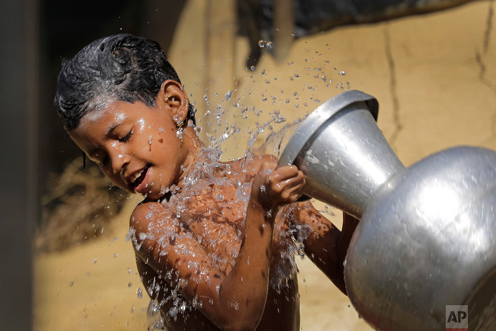 """A Rohingya Muslim pours water on herself as she bathes outside her tent in Kutupalong Refugee camp on Monday, Nov. 20, 2017, in Bangladesh. More than 620,000 Rohingya have fled Rakhine for neighboring Bangladesh since late August, when the military launched what it called """"clearance operations"""" in response to insurgent attacks. (AP Photo/Wong Maye-E)"""