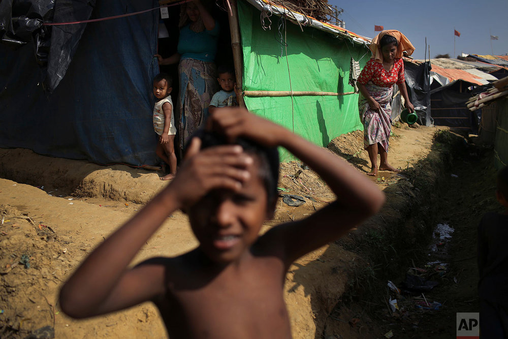 """A Rohingya boy plays outside his family's tent in Kutupalong refugee camp on Saturday, Nov. 25, 2017, in Bangladesh.  The United Nations and others have said the military's actions appeared to be a campaign of """"ethnic cleansing,"""" using acts of violence and intimidation and burning down homes to force the Rohingya to leave their communities, with more than 600,000 Rohingya fleeing to Bangladesh. (AP Photo/Wong Maye-E)"""