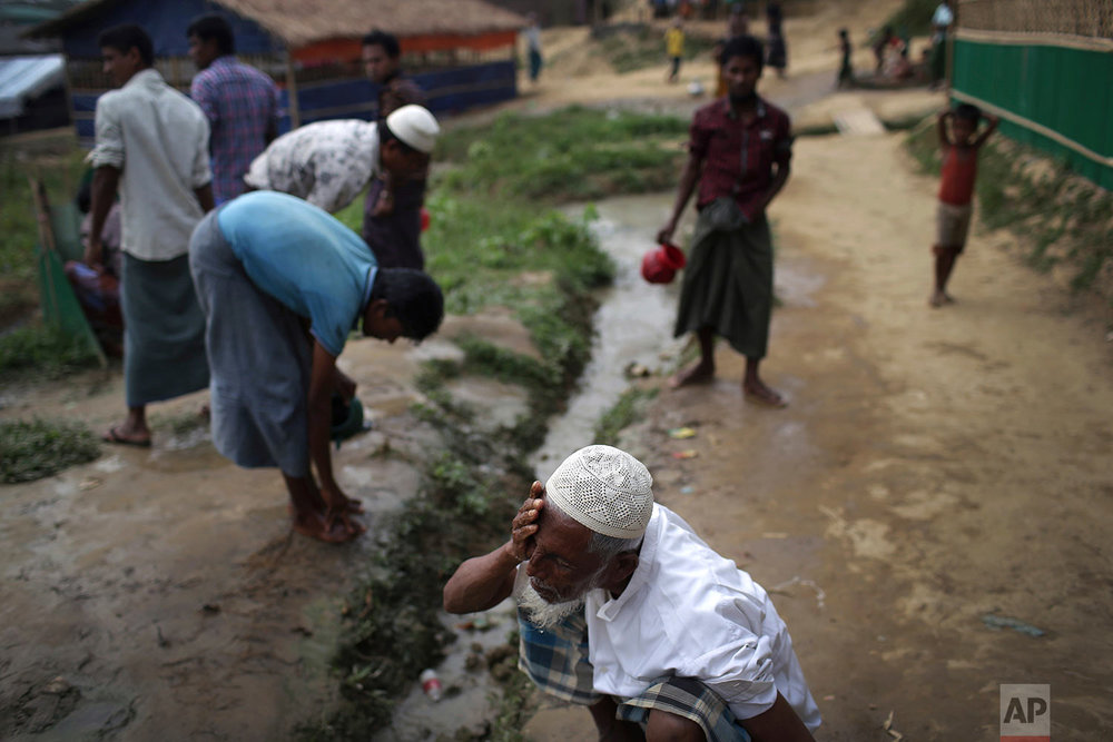 """A Rohingya Muslim man washes his face before Friday prayers outside a makeshift mosque in Jamtoli refugee camp on Friday, Nov. 24, 2017, in Bangladesh. Since late August, more than 620,000 Rohingya have fled Myanmar's Rakhine state into neighboring Bangladesh, seeking safety from what the military described as """"clearance operations."""" The United Nations and others have said the military's actions appeared to be a campaign of """"ethnic cleansing,"""" using acts of violence and intimidation and burning down homes to force the Rohingya to leave their communities. (AP Photo/Wong Maye-E)"""