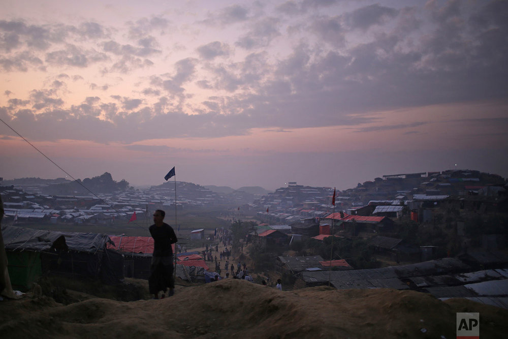 """A Rohingya Muslim man is silhouetted against the dusk sky in Jamtoli refugee camp on Friday, Nov. 24, 2017, in Bangladesh. Since late August, more than 620,000 Rohingya have fled Myanmar's Rakhine state into neighboring Bangladesh, seeking safety from what the military described as """"clearance operations."""" The United Nations and others have said the military's actions appeared to be a campaign of """"ethnic cleansing,"""" using acts of violence and intimidation and burning down homes to force the Rohingya to leave their communities. (AP Photo/Wong Maye-E)"""