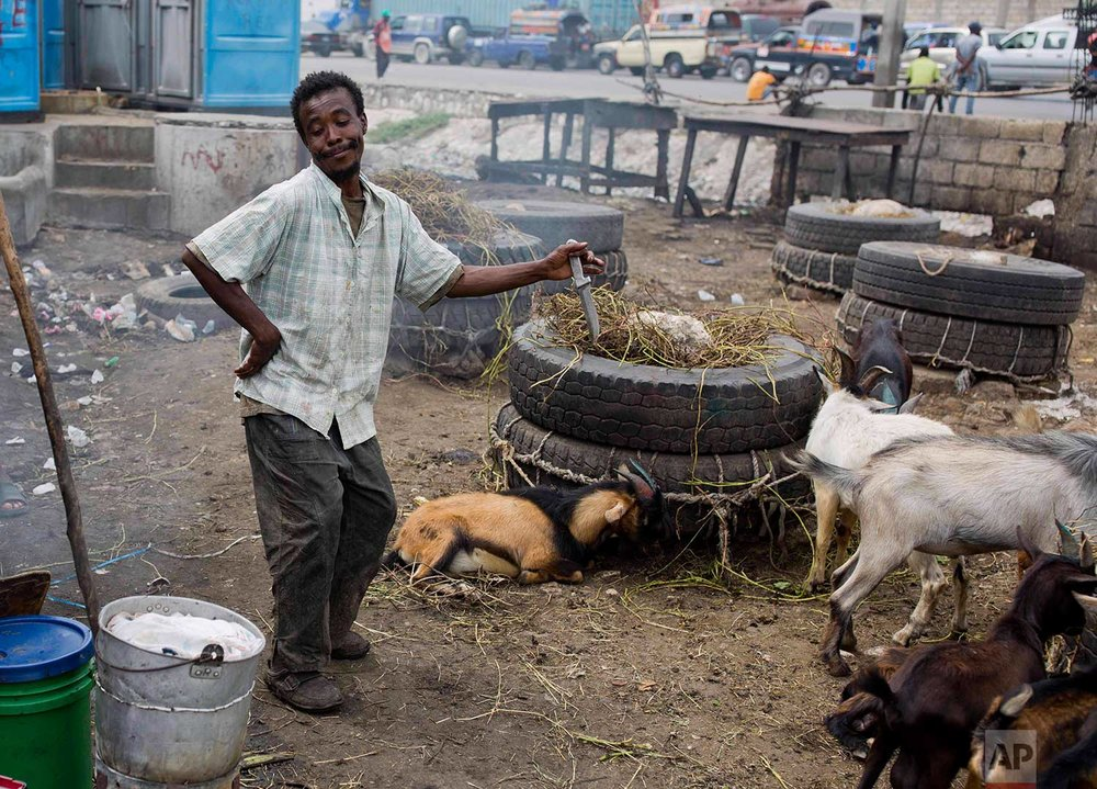 In this Nov. 10, 2017 photo, Difisil Michel does a jig as his work day comes to an end at the La Saline slaughterhouse, in Port-au-Prince, Haiti. Michel, a former cabinetmaker, has worked at the market 11 years, scraping the hair from goat heads and hooves. The 30-year-old would like to see authorities construct a modern-day slaughterhouse that would provide change rooms and shower facilities so he doesn't have to go home smelling like a dead animal. (AP Photo/Dieu Nalio Chery)
