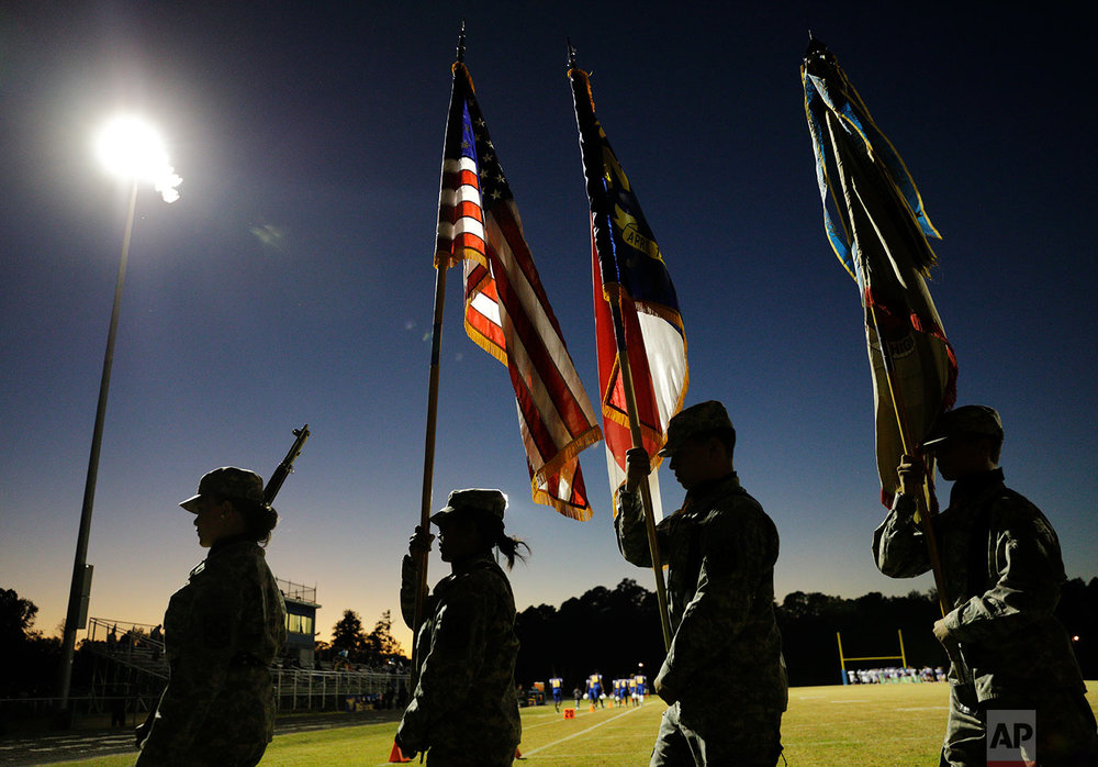 Members of a color guard walk off the field following the national anthem at a football game at South Robeson High School in Rowland, N.C., Friday, Oct. 27, 2017. (AP Photo/David Goldman)